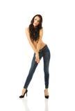Hemdlose Frau in voller Länge, die in den Jeans anzieht stockfotografie