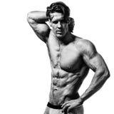 Hemdloser Bodybuilder, der seine muskulösen Arme zeigt Stockfotos