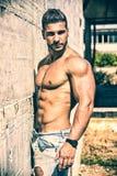 Hemdloser Bodybuilder gegen Betonmauer stockbild