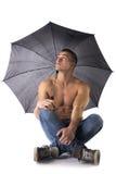 Hemdloser junger Mann, der Regenschirm hält und oben schaut Stockfotografie