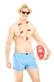 Hemdloser Mann in den Schwimmenkurzen hosen, Holding ein Wasserball Stockfotos