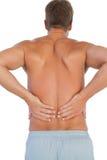 Hemdloser Mann, der unter niedrigeren Rückenschmerzen leidet Stockfotografie