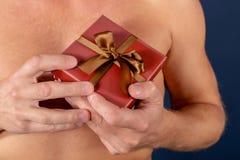 Hemdloser Mann hält eine Geschenkbox lokalisiert auf Weiß Überraschung Schönes Tanzen der jungen Frau der Paare Feiertag und spez lizenzfreies stockbild