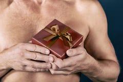 Hemdloser Mann hält eine Geschenkbox lokalisiert auf Weiß Überraschung Schönes Tanzen der jungen Frau der Paare Feiertag und spez stockbilder