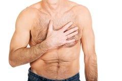 Hemdloser Mann mit Schmerz in der Brust Stockbilder