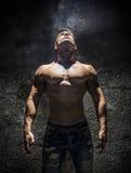 Hemdloser Muskel-Mann, der oben helles obenliegendes Licht untersucht Lizenzfreies Stockbild