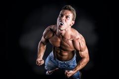 Hemdloser Muskel-Mann mit den spitzen Zähnen heulend Stockfotografie