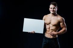 Hemdloser muskulöser junger Mann, der eine leere horizontale weiße Fahne zeigt Finger auf das copyspace für Ihr halten steht Lizenzfreie Stockfotos