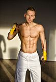 Hemdloser muskulöser junger Mann, der mit springendem Seil steht Lizenzfreies Stockfoto
