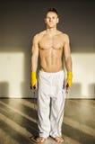 Hemdloser muskulöser junger Mann, der mit springendem Seil steht Stockfoto