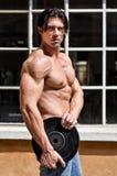 Hemdloser muskulöser Mann, der Gewichtsdiskette hält Lizenzfreie Stockfotos