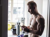 Hemdloser muskulöser Mann, der Handy in der Turnhalle verwendet Lizenzfreie Stockfotos