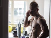 Hemdloser muskulöser Mann, der Handy in der Turnhalle verwendet Stockbild