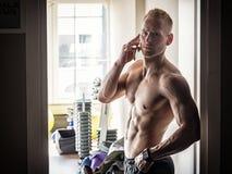 Hemdloser muskulöser Mann, der Handy in der Turnhalle verwendet Lizenzfreies Stockbild