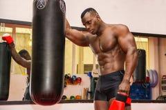 Hemdloser muskulöser männlicher Boxer, der nahe bei Sandsack stillsteht Stockfoto