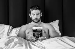 Hemdloser sexy hunky Mann mit Bart liegt im Bettlesebuch stockfotografie