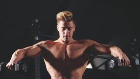 Hemdloser weißer Mann, der Übung mit Dummkopfgewicht in der dunklen Turnhalle beginnt stock footage