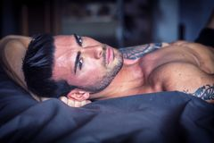 Hemdloses sexy männliches Modell, das allein auf seinem Bett liegt lizenzfreie stockbilder