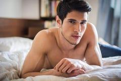 Hemdloses sexy männliches Modell, das allein auf seinem Bett liegt stockbilder