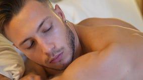 Hemdloses sexy männliches Modell, das allein auf seinem Bett liegt stock video footage
