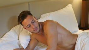 Hemdloses sexy männliches Modell, das allein auf seinem Bett liegt stock footage