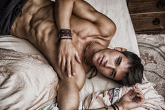 Hemdloses sexy männliches Modell, das allein auf seinem Bett liegt Stockbild