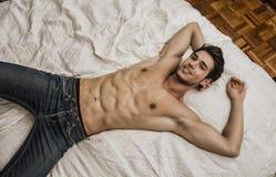 Hemdloses sexy männliches Modell, das allein auf seinem Bett liegt stockfotos