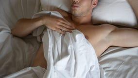 Hemdloses sexy männliches Modell, das allein auf seinem Bett liegt stock video