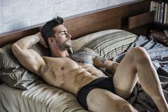 Hemdloses sexy männliches Modell, das allein auf seinem Bett liegt lizenzfreie stockfotos