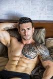 Hemdloses sexy männliches Modell, das allein auf seinem Bett liegt stockfotografie