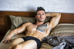 Hemdloses sexy männliches Modell, das allein auf seinem Bett liegt lizenzfreie stockfotografie