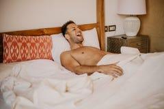 Hemdloses sexy männliches Modell, das allein auf seinem Bett in seinem Schlafzimmer liegt Sorgloser Kerl, der neuen Tag genießt stockbilder