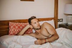 Hemdloses sexy männliches Modell, das allein auf seinem Bett in seinem Schlafzimmer, weg schauend mit einer verlockenden Haltung  stockfoto