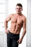 Hemdloses sexy männliches Modell, das im Eingangsausgangsinnenraum, schauend zur Kamera mit einer verlockenden Haltung steht Lizenzfreie Stockfotos
