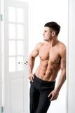 Hemdloses sexy männliches Modell, das im Eingangsausgangsinnenraum, weg schauend mit einer verlockenden Haltung steht Lizenzfreie Stockfotografie