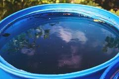 Hemel en boombezinning in het blauwe watervat Stock Afbeeldingen