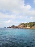 Hemel en overzees met rotsachtig eiland stock afbeeldingen