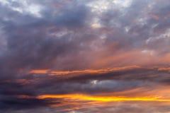 Hemel met grijze en blauwe wolken en rood-oranje hoogtepunt van de Zon, achtergrond royalty-vrije stock foto's