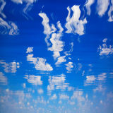 Hemel met wolken die in water worden weerspiegeld Stock Foto's