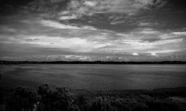 Hemel over zwart-wit water royalty-vrije stock afbeelding