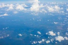 Hemel, wolken en grond uit het venster van het vliegtuig wordt genomen dat Royalty-vrije Stock Afbeelding