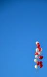 Hemelachtergrond met een bos van rode en witte ballons Stock Fotografie