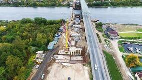 Hemelmening van actieve brugbouw bij gebieds nabijgelegen rijweg en rivier stock videobeelden