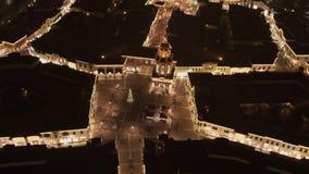 Hemelmening van leuk vierkant met verlichte verfraaide pijnboomboom in de winteravond stock videobeelden
