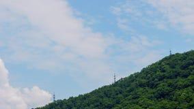 Hemelwolk timelapse op achtergrond van hoogspanningstoren op groene berg stock videobeelden