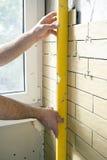 Hemförbättring - faktotumet mäter straightness av väggen royaltyfria foton