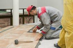 Hemförbättring renovering - byggnadsarbetaretileren är tilien Arkivbilder