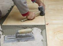 Hemförbättring renovering - byggnadsarbetaretileren belägger med tegel, bindemedel för golvet för den keramiska tegelplattan, mur arkivbilder