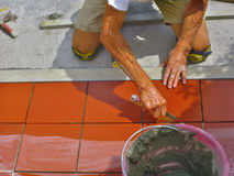 Hemförbättring renovering - byggnadsarbetaretileren belägger med tegel, bindemedel för golvet för den keramiska tegelplattan Arkivbild