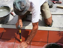 Hemförbättring renovering - byggnadsarbetaretileren belägger med tegel, bindemedel för golvet för den keramiska tegelplattan Royaltyfri Bild